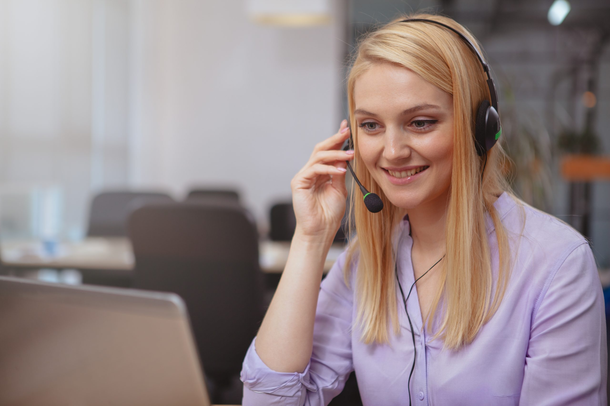Beautiful cheerful woman smiling joyfully, answering customer calls at the call center, typing on her laptop. Lovely female customer support operator talking with callers, wearing headset